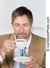 Businessman With Eyes Closed Enjoying Coffee In Office