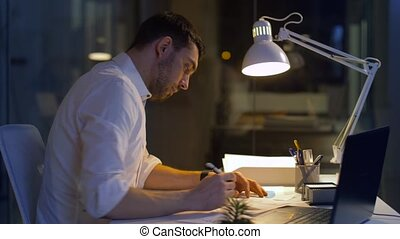 businessman with files and laptop working at night