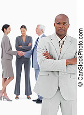 Businessman with folded arms and trading partners behind him