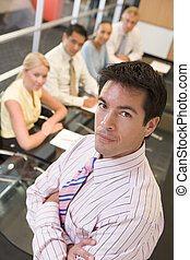 Businessman with four businesspeople at boardroom table in backg