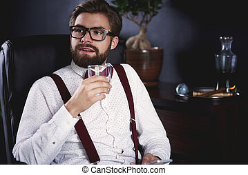Businessman with glass of whiskey relaxing