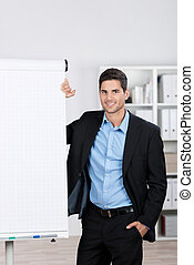 Businessman With Hand In Pocket Standing By Flip Chart