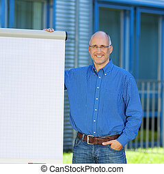 Businessman With Hand In Pocket Standing By Flipchart