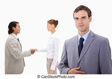 Businessman with hand shaking colleagues behind him