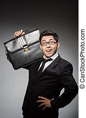Businessman with handbag against gray