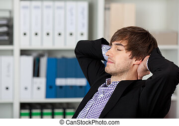 Businessman With Hands Behind Head And Closed Eyes
