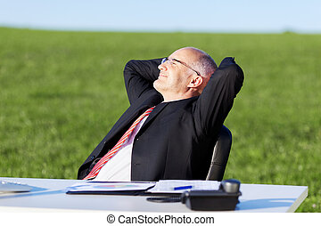 Businessman With Hands Behind Head At Desk On Field