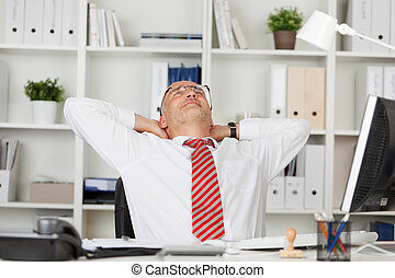 Businessman With Hands Behind Head At Desk