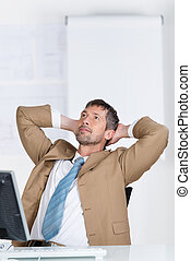 Businessman With Hands Behind Head Looking Up At Desk