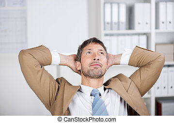 Businessman With Hands Behind Head Looking Up In Office