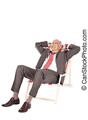 Businessman With Hands Behind Head Relaxing On Deck Chair