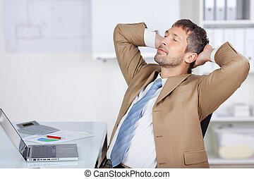 Businessman With Hands Behind Head Sleeping At Desk