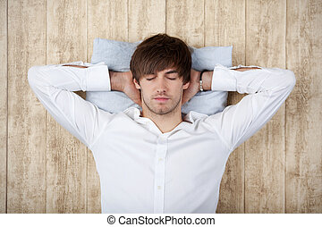 Businessman With Hands Behind Head Sleeping On Wooden Wall
