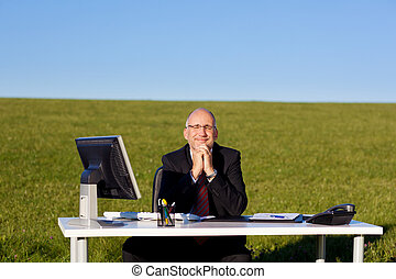 Businessman With Hands Clasped Sitting At Desk On Field