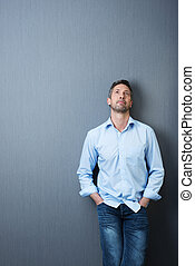 Businessman With Hands In Pockets Looking Up Against Blue Wall