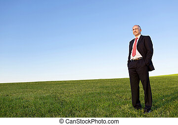 Businessman With Hands In Pockets On Grassy Field Against Sky