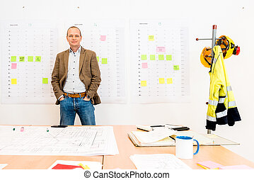 Businessman With Hands In Pockets Standing By Blueprint On Table