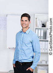 Businessman With Hands In Pockets Standing In Office