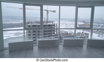 rear back view manager in real estate developer. employer in contemporary company looking through the windows in modern office on the construction site. urban landscape in winter season. man oversees building.