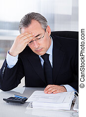 Businessman With Headache In Office