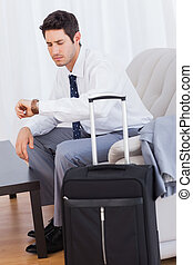 Businessman with his baggage waiting for flight sitting on sofa at office