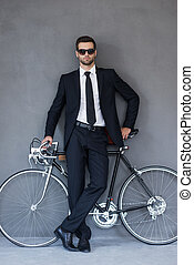 Businessman with his bicycle. Full length of handsome young businessman leaning at the bicycleand looking at camera while standing against grey background