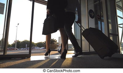Businessman with his female colleague leaving terminal through glass doors and roll suitcase on wheels. Business man and woman going from the airport to city street with their luggage. Slow motion