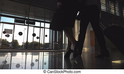 Businessman with his female colleague walking to the exit from terminal and roll suitcase on wheels. Business man and woman stepping at the airport or office building. Travel concept. Slow motion