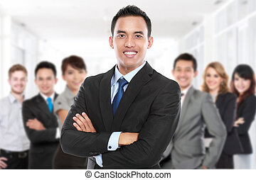Businessman with his team member behind. smiling with ...