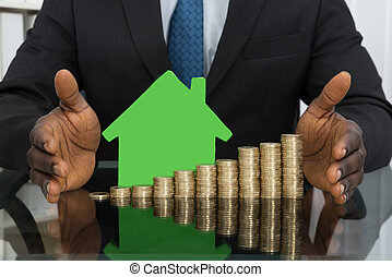 Businessman With House Model And Coins