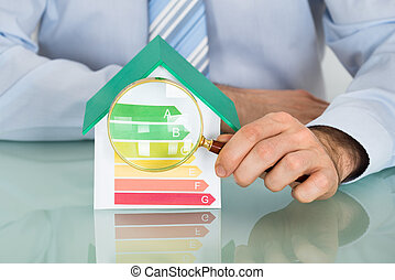 Businessman With House Model And Magnifying Glass