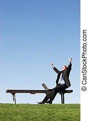 Businessman with laptop 60 - Business man raises arms in...