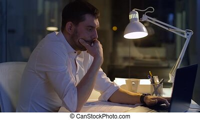 businessman with laptop and coffee at night office