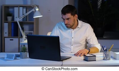 businessman with laptop and papers at night office -...