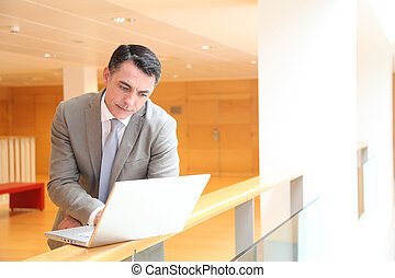 Businessman with laptop computer waiting in hall