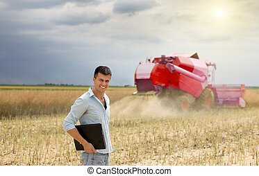 Businessman with laptop in field