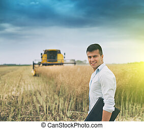 Businessman with laptop in front of combine harvester