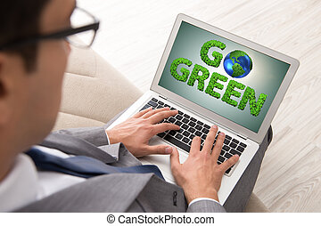 Businessman with laptop in green environment concept