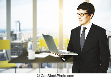 Businessman with laptop in modern office
