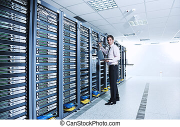 businessman with laptop in network server room - young ...