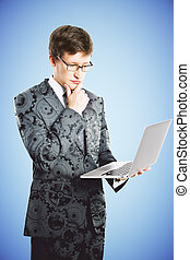 Businessman with laptop in suit with gears