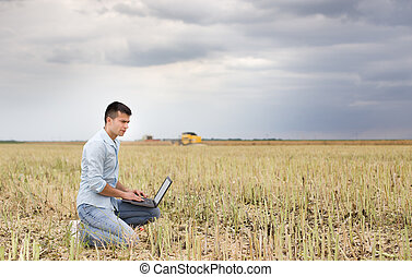 Businessman with laptop in the field