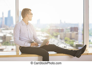 Businessman with laptop looking at city