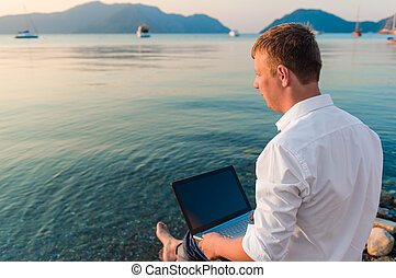businessman with laptop looking at the sea
