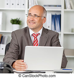 Businessman With Laptop Looking Away In Office