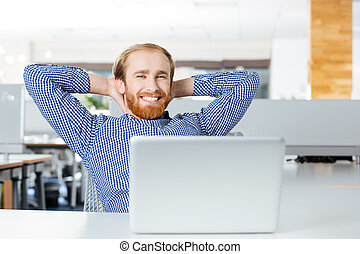Businessman with laptop sitting on workplace holding hands behind head