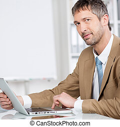 Businessman With Laptop Smiling At Desk