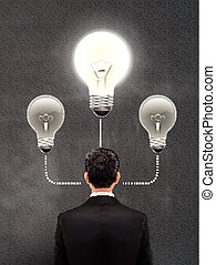 businessman with lighting bulb above head over grey