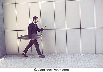 Businessman with longboard and mobile phone - Toned image of...