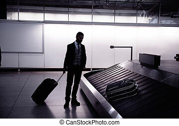 Businessman with luggage at the airport, at conveyor belt